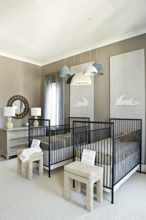 a creative twin nursery with grey walls, black metal cribs, grey stools, crochet pendant lamps and a grey dresser