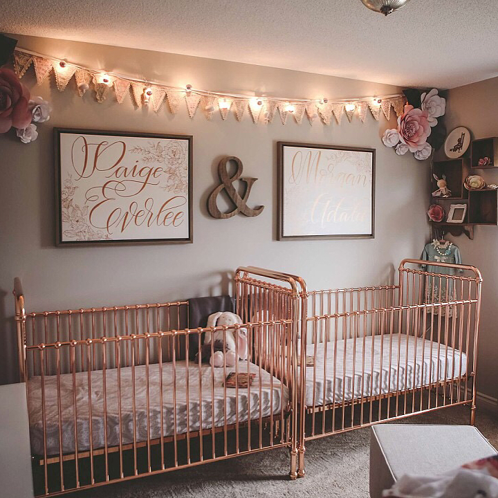 a cute and glam twin nursery with grey walls, rose gold cribs, a bunting and lights, pretty artworks and paper flowers