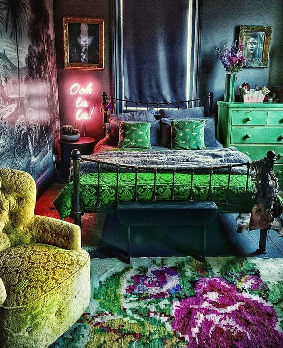 a dark maximalist bedroom with navy and grey walls, a forged bed, a green dresser, a neon light, statement artworks and a bold floral rug