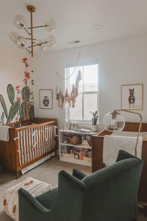 a desert themed twin nursery with stained cribs, cactus on the wall and dresser, a catchy chandelier and a green chair