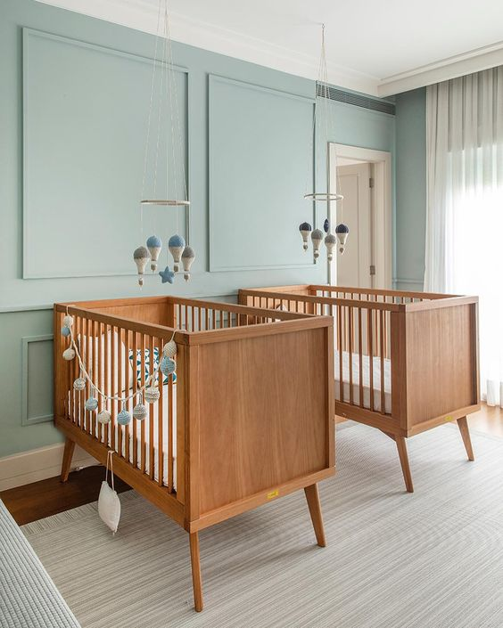 a dreamy twin nursery with blue paneled walls, lovely stained cribs, mobiles and neutral textiles is a very welcoming space