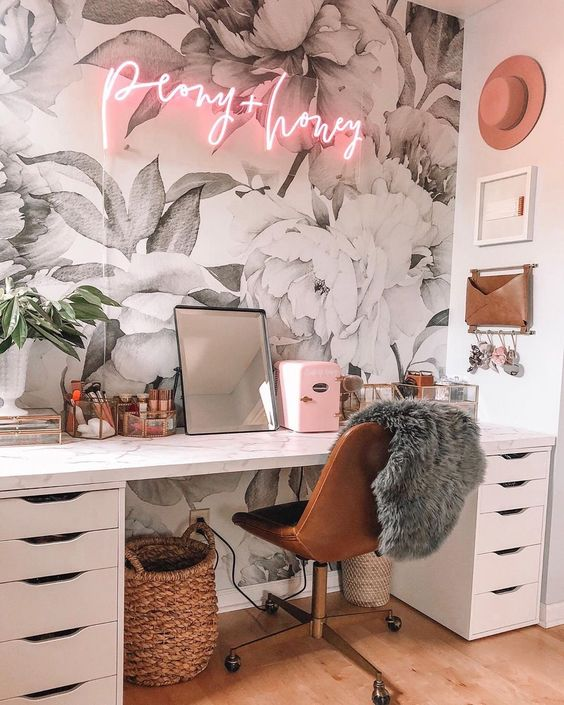 a fancy and glam home office with a floral wallpaper wall, a white desk, a leather chair, a pink neon light and a mirror