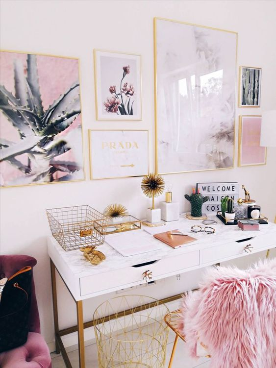 a fancy and glam home office with a white desk, a gold chair with pink faux fur, a lovely glam gallery wall in gold frames