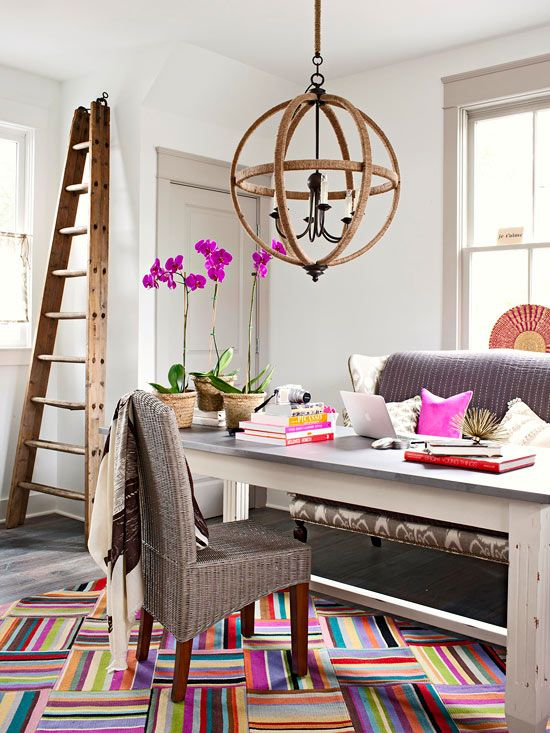a fancy and whimsy home office with a grey sofa and woven chair, a large desk, a sphere chandelier, a ladder and colorful touches