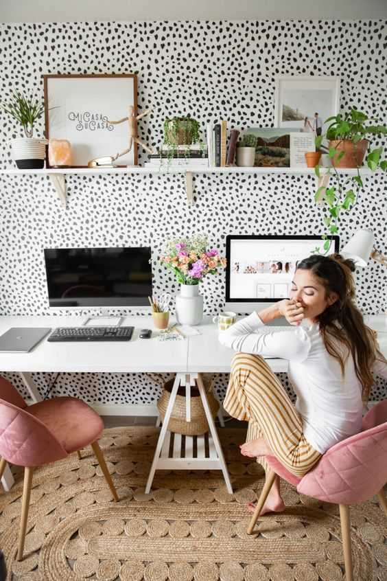 a fancy home office with a Dolmatin accent wall, a shared trestle desk, pink chairs, a long shelf and potted greenery
