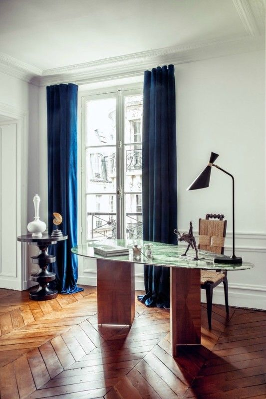 a fancy home office with a beautiful wood and marble desk, a woven chair, a black side table and navy curtains