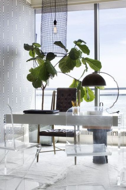 a fancy home office with a concrete and acryl desk, acrylic chairs and a leather one, a bold potted plant and a unique light