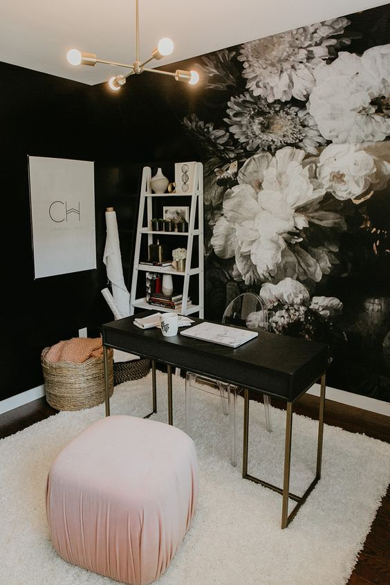 a fancy home office with a dark floral wall, a black and brass desk, a clear chair, a pink pouf and a basket plus a ladder shelving unit