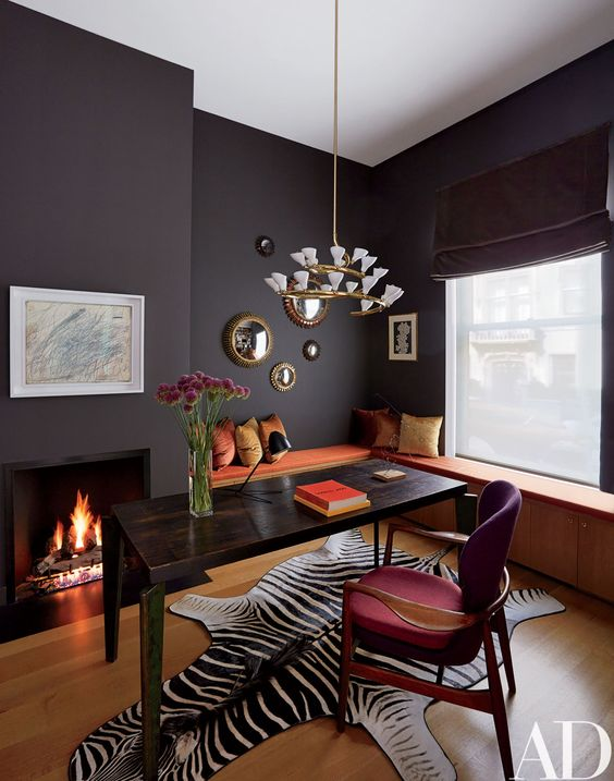 a fancy home office with a storage windowsill seating, a black desk, a fuchsia chair, a built-in fireplace and a lovely chandelier