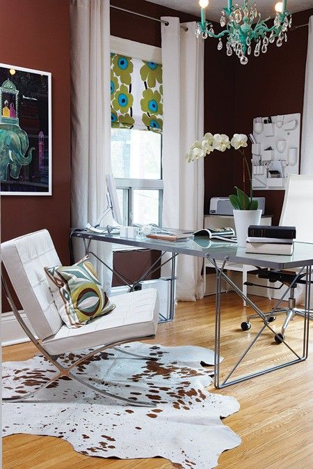 a fancy home office with an industrial desk, chic white chairs, black and burgundy walls, a turquoise chandelier and a printed shade