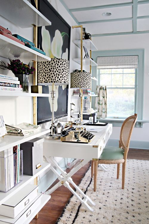 a fancy home office with light blue and white walls, a refined trestle desk, a rattan chair, open storage units and a statement floral artwork