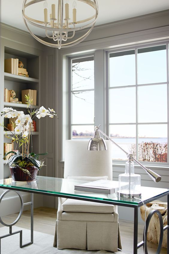 a fancy home office with light grey paneling, a glass desk and a creamy chair, built-in shelves and a sphere chandelier