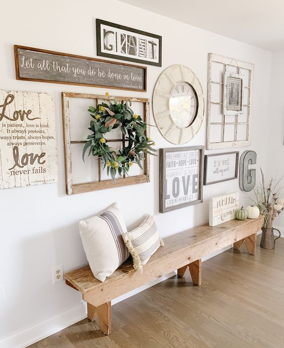 a farmhouse gallery wall with a clock in a thick frame, a window frame with a wreath, some plaques and metal monograms is cute