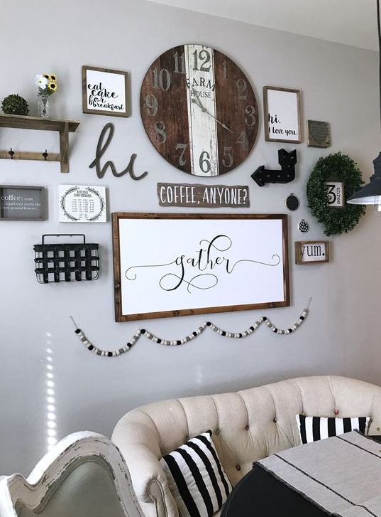 a farmhouse gallery wall with a shelf, a greenery wreath, arrows, a wooden clock, some signs in frames and a wooden bead garland is cool