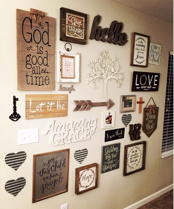 a farmhouse gallery wall with various signs and artworks, arrows, keys, hearts and words is very chic and cool