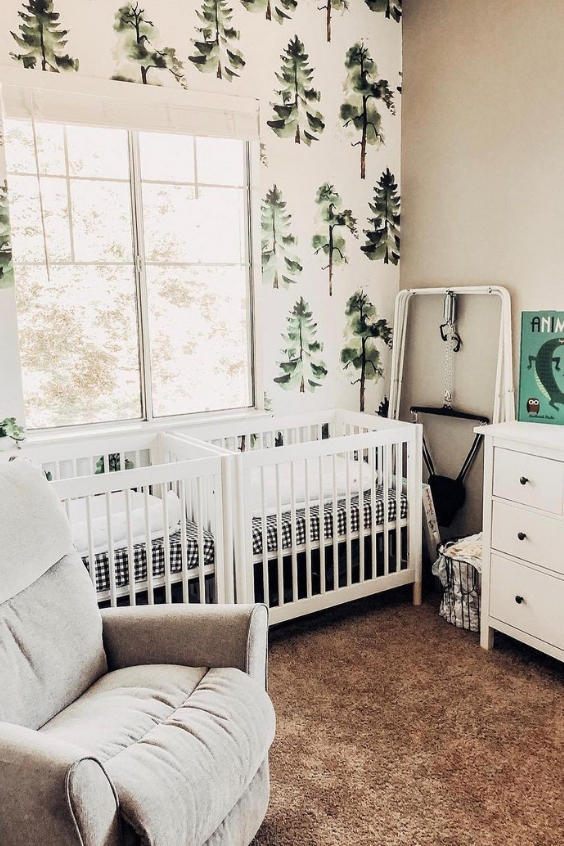 a forest-themed twin nursery with white cribs, tree-printed wallpaper, white and grey furniture and a pretty soft rug