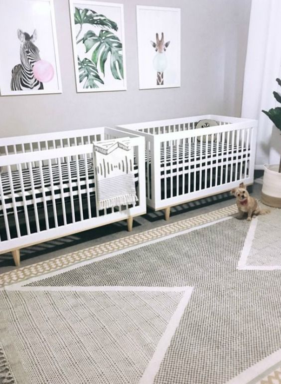 a fun contemporary twin nursery with two white cribs, a gallery wall, printed textiles and a potted plant is cool