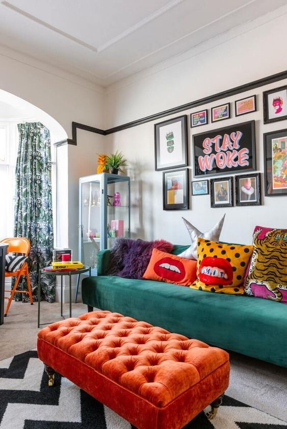a fun maximalist living room with a green sofa and a coral ottoman, a bright gallery wall and colorful pillows plus printed textiles