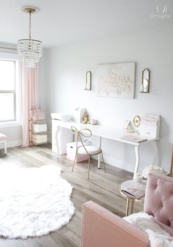 a glam and girlish home office in neutrals, with a desk and a whimsy chair, pink textiles and a tufted armchair, a crystal chandelier and a pretty rug