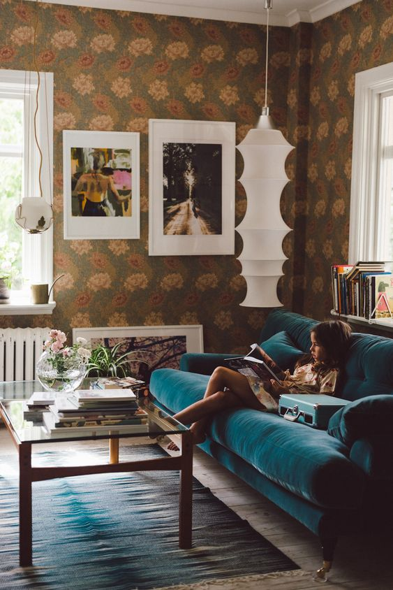 a gorgeous eclectic living room with bold floral wallpaper, a modern turquoise sofa, a glass table and a pretty gallery wall