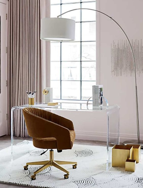 a gorgeous home office with an acrylic desk, a mustard chair, gold boxes, blush walls and matching curtains plus a floor lamp