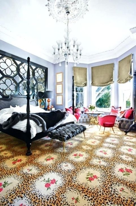 a gorgeous maximalist bedroom with lilac walls, a black bed and an ottoman, red chairs and a grey windowsill bench, a crystal chandelier