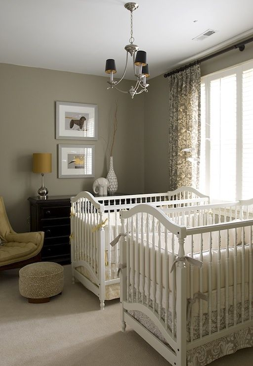 a grey and yellow mid-century modern nursery with white cribs, a black dresser, a chic chandelier and a yellow chair