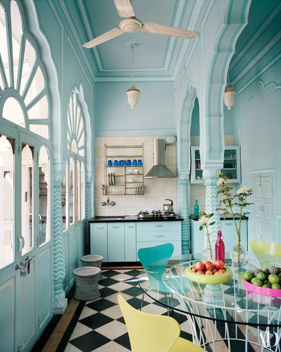 a light blue Moroccan style kitchen with black countertops, a checked floor, a round glass table, yellow and blue chairs