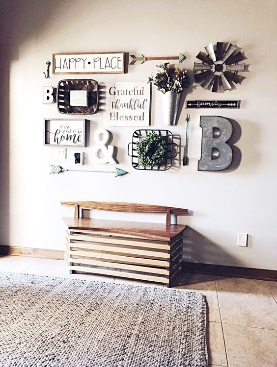a lovely farmhouse gallery wall with signs in frames, a metal monogram, some potted blooms and metal elements