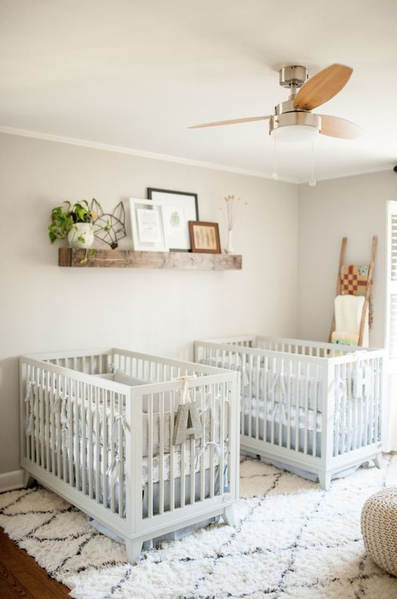 a lovely farmhouse twin nursery with grey walls, white cribs, a stained shelf with artworks and potted greenery plus a ladder