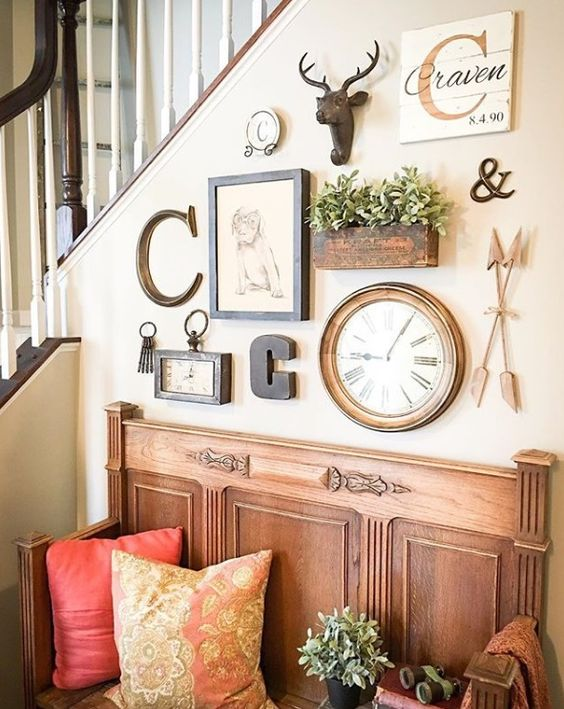 a lovely gallery wall with a clock, some artworks, monograms, potted greenery and faux taxidermy is a stylish solution