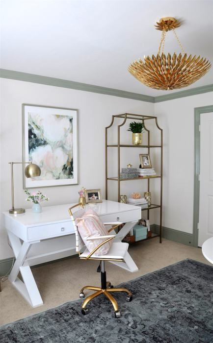 a lovely home office with a white desk, a white and gold chair, an open shelving unit, a gold chandelier and a floral artwork