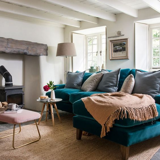 a lovely living room with a hearth with a wooden beam, a turquoise sofa, neutral textiles, a pink ottoman and a vintage lamp
