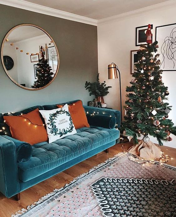 a lovely living room with a turquoise sofa, a Christmas tree with lights, a floor lamp and a round mirror plus a printed rug