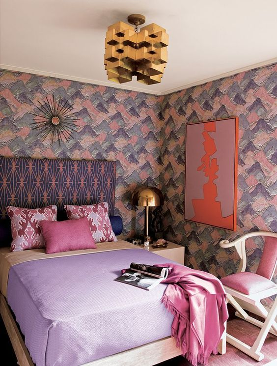a lovely maximalist bedroom with brushstroke walls, a printed bed, pastel bedding, a pink chair, a gold sculptural chandelier