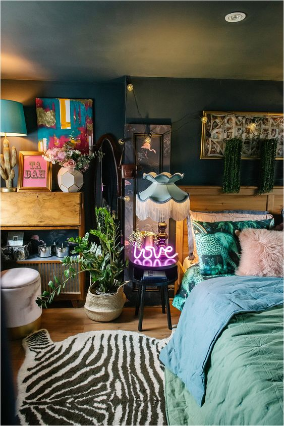 a lovely maximalist bedroom with dark walls and a ceiling, with mid-century modern furniture, pastel bedding, a potted plant, a neon light and colorful artworks