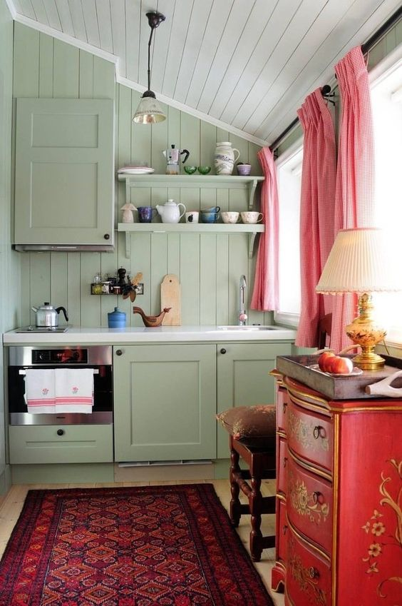 a lovely maximalist kitchen with olive green walls and a kitchen, a red dresser, a refined stool, pink curtains and a bright rug