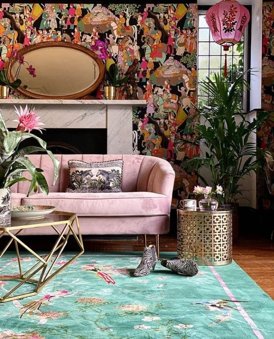 a lovely maximalist living room with a bold printed accent wall, a pink sofa, a green rug, metallic pieces and potted plants