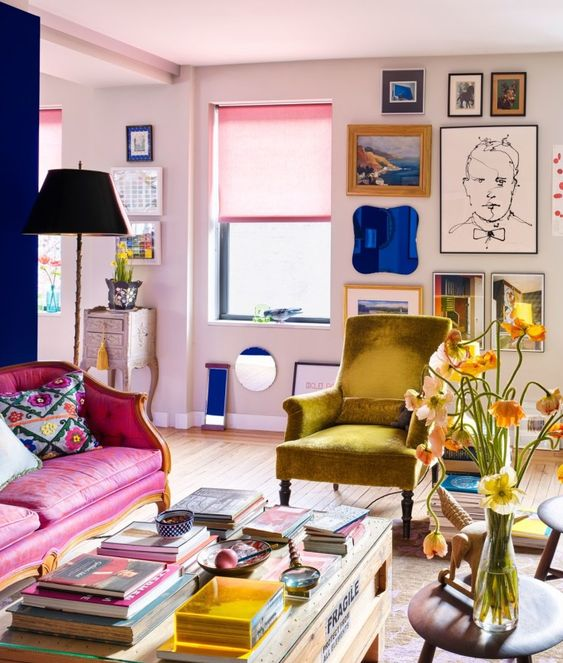 a lovely maximalist living room with blush walls, a hot pink sofa, a mustard chair, a coffee table with lots of books and a bright gallery wall