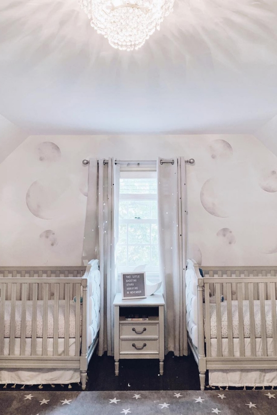 a lovely neutral nursery with lunar stenciled walls, grey cribs, a layered rugs and grey glitter curtains is very chic