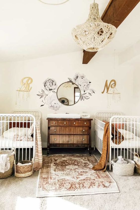 a lovely nursery with a wooden beam on the ceiling, white cribs, a stained dresser, a boho rug and textiles plus baskets for storage