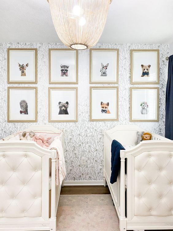 a lovely nursery with ana ccent wall, white tufted cribs, a gallery wlal with animal and navy black-out curtains