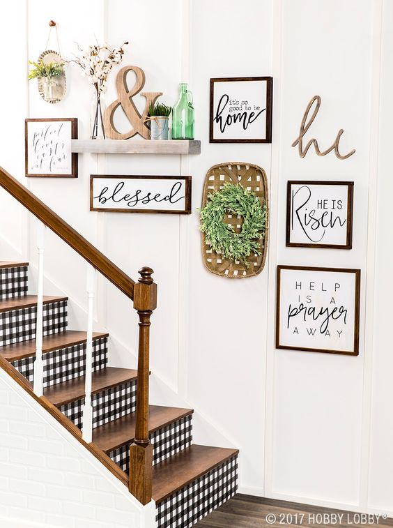 a lovely rustic gallery wall with signs in stained frames, a greenery wreath, a shelf with potted grass and an ampersand and a green bottle