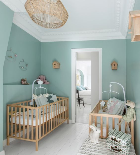 a lovely twin nursery with green walls, matching stained cribs, matching mobiles and a rattan pendant lamp