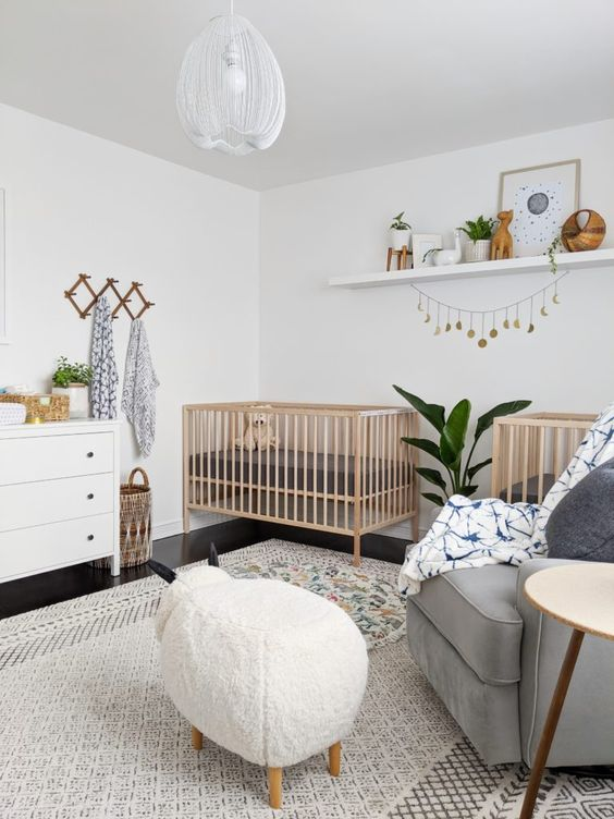 a lvoely neutral nursery with stained cribs, a grey chair, an animal-shaped ottoman, a white dresser, a shelf with artworks