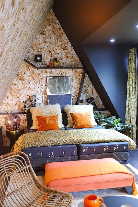 a maximalist attic bedroom with botanical walls and a black one, a navy bed, a coral ottoman, bright bedding and shelves