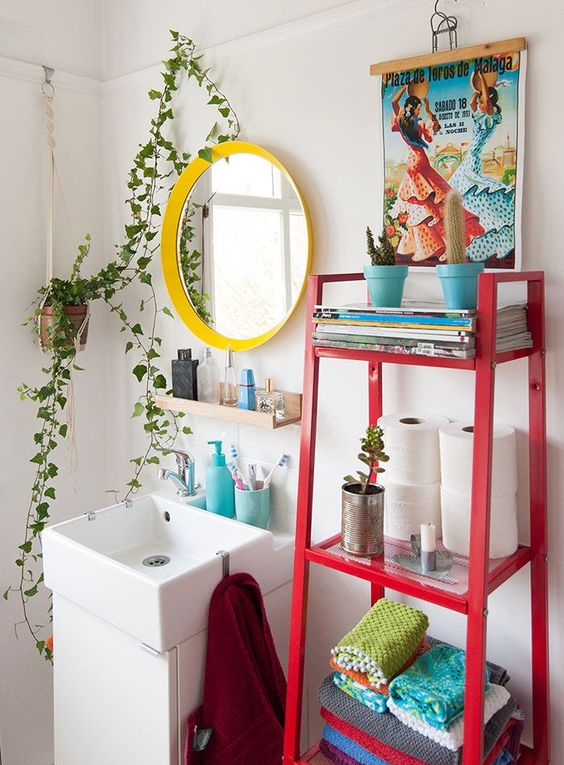a maximalist bathroom with a yellow frame mirror, a red ladder with decor and a colorful artwork plus potted greenery