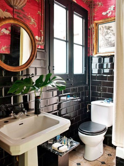 a maximalist bathroom with black subway tiles, red printed wallpaper, a round mirror, artworks and white appliances