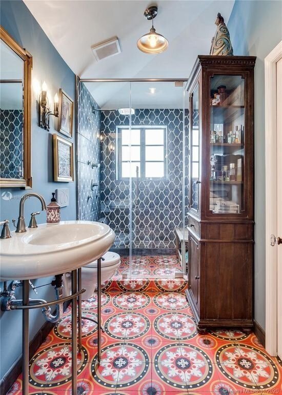 a maximalist bathroom with blue walls and blue tiles, a red mosaic tile floor, a stained storage cabinet and a smal gallery wall