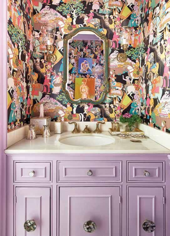 a maximalist bathroom with crazily printed wallpaper, a lilac built-in vanity and a mirror in a vintage frame is chic